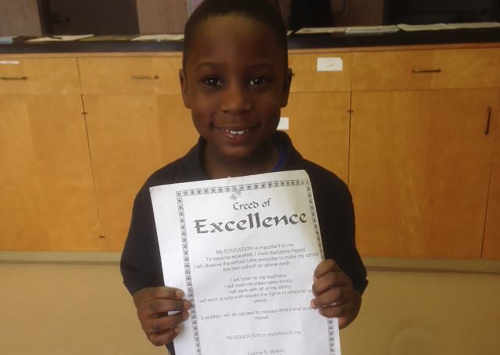 young boy holding his certificate of excellence at a Preschool & Daycare Serving Toledo, OH