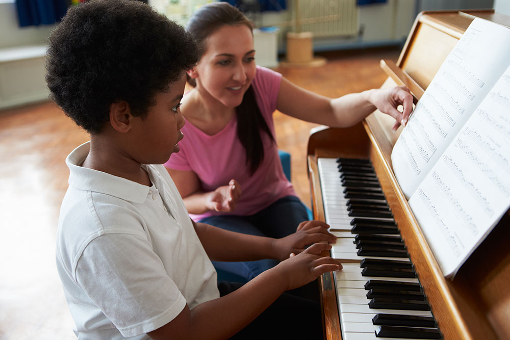 Male Student Enjoying Piano Lesson With Teacher at a Elementary School Serving Toledo, OH