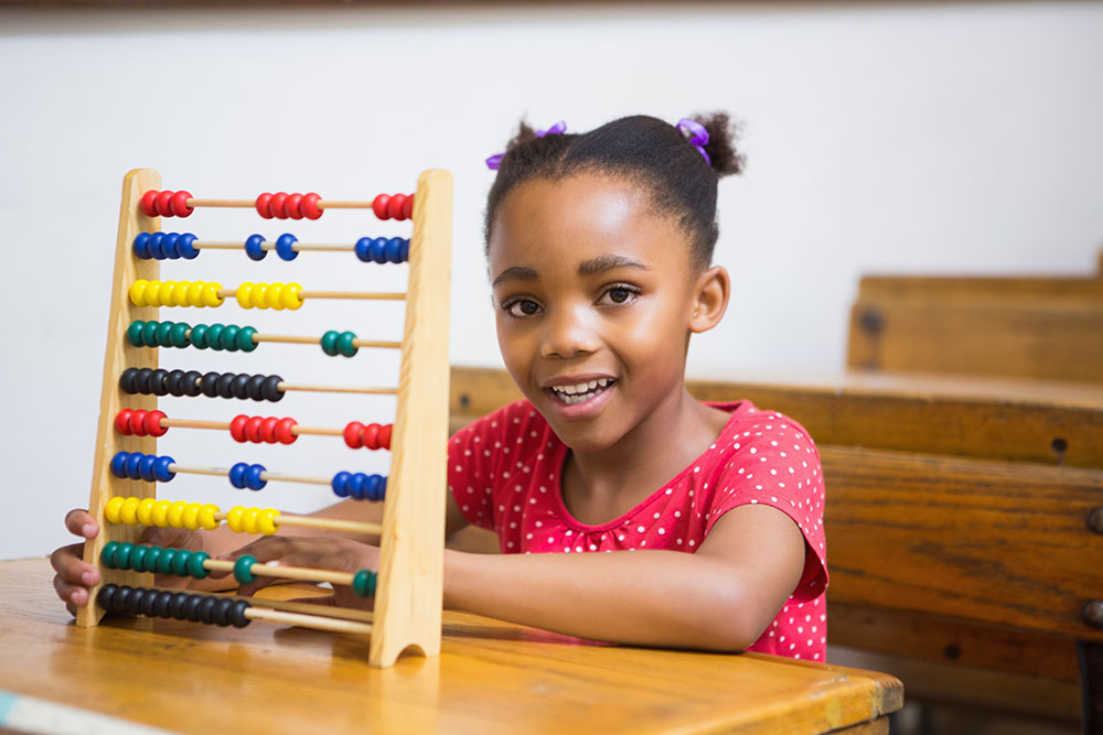 Smiling pupil using abacus in classroom at a Elementary School Serving Toledo, OH