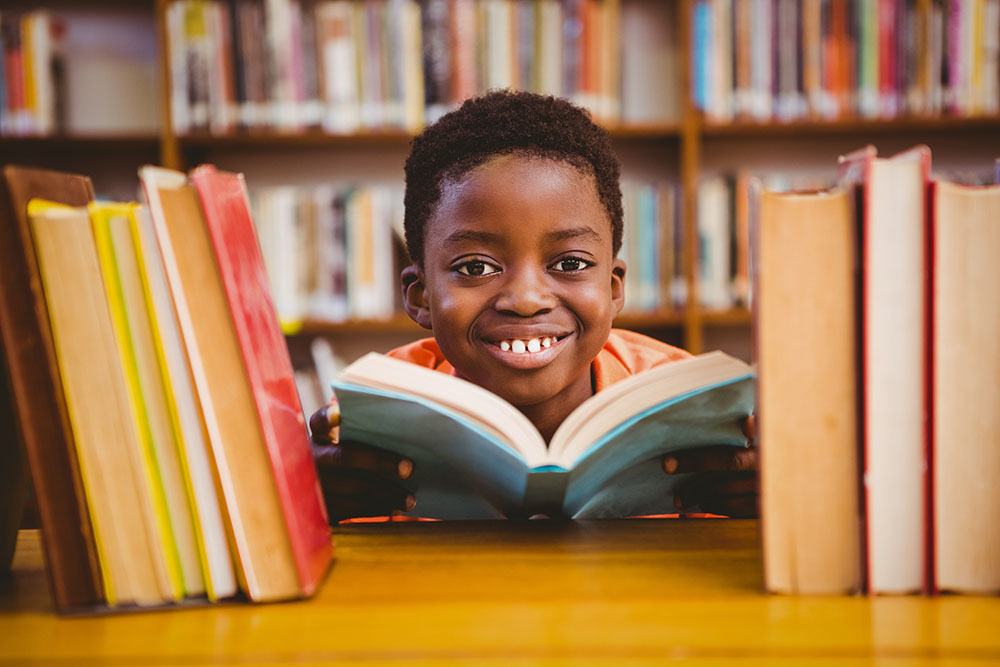 smiling boy reading a book at a Elementary School Serving Toledo, OH